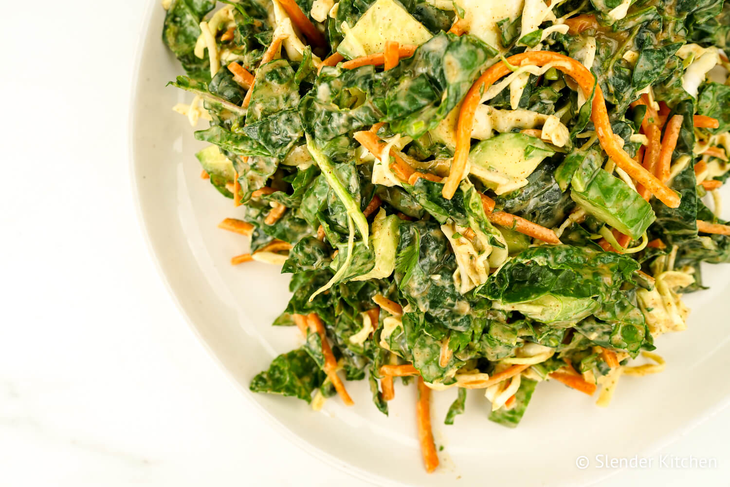 Kale slaw with apples, cucumbers, and fresh herbs on a white ceramic plate.