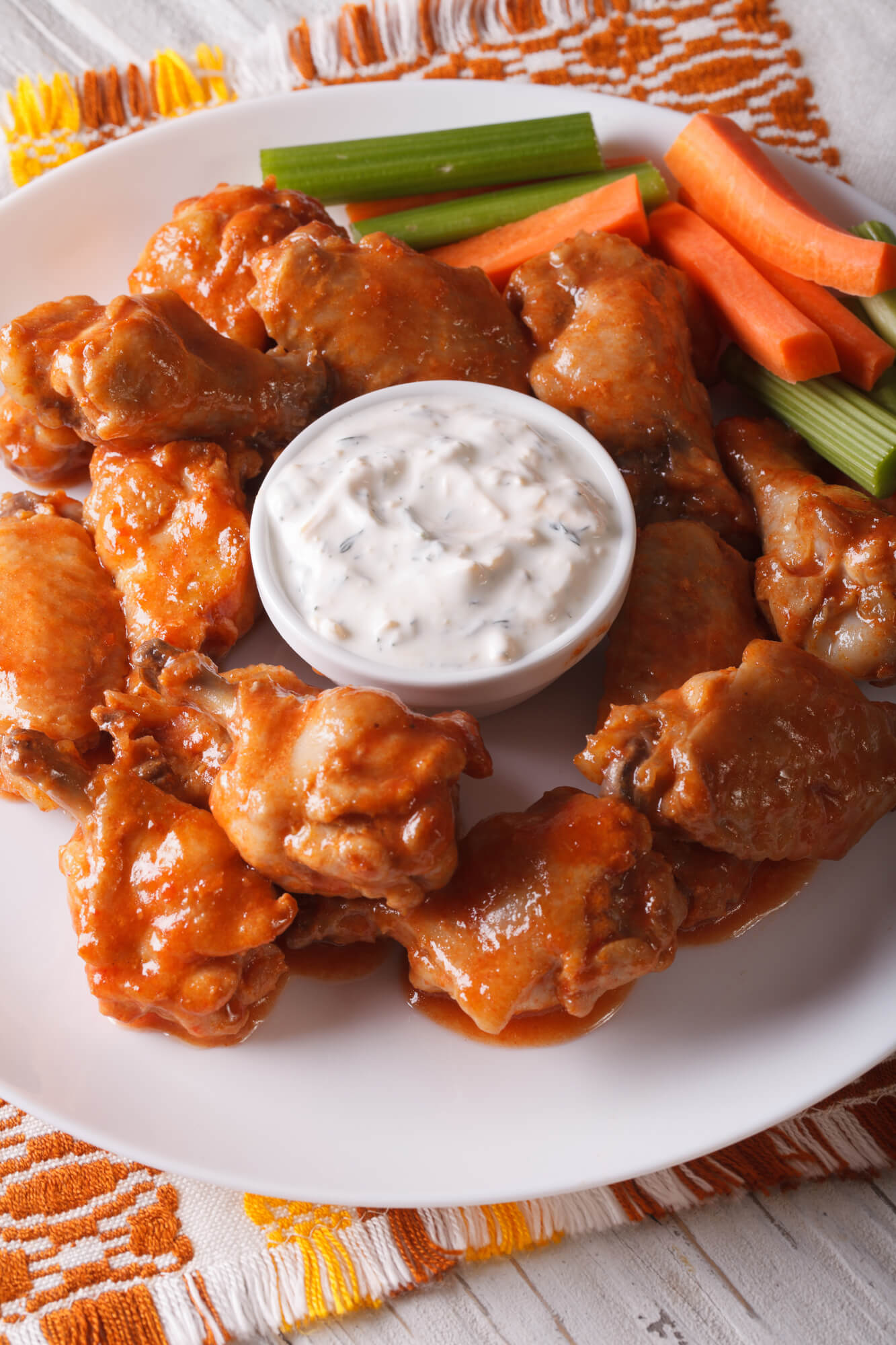 Baked buffalo wings recipe with ranch dressing on a red napkin.