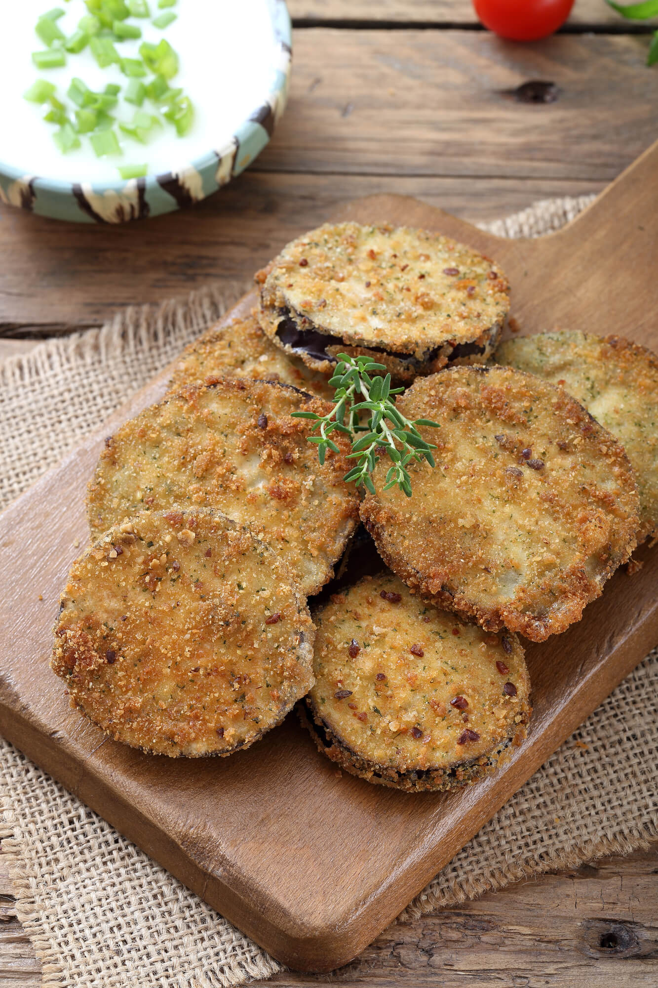 Baked eggplant cutlets on a cutting board with fresh herbs.