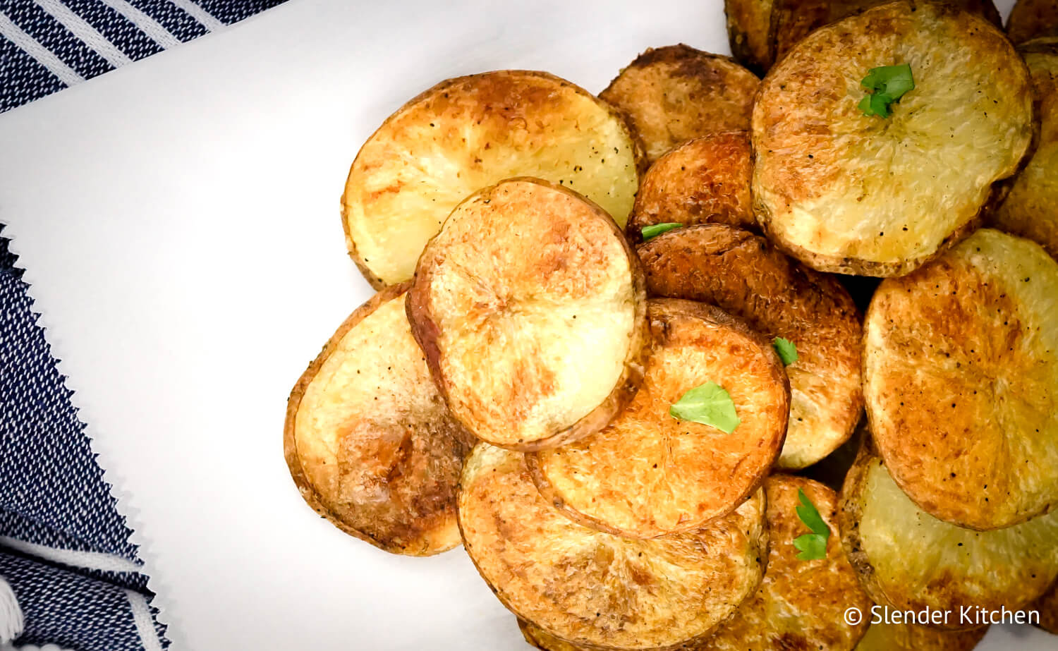 Healthy potato chips on parchment paper with parsley