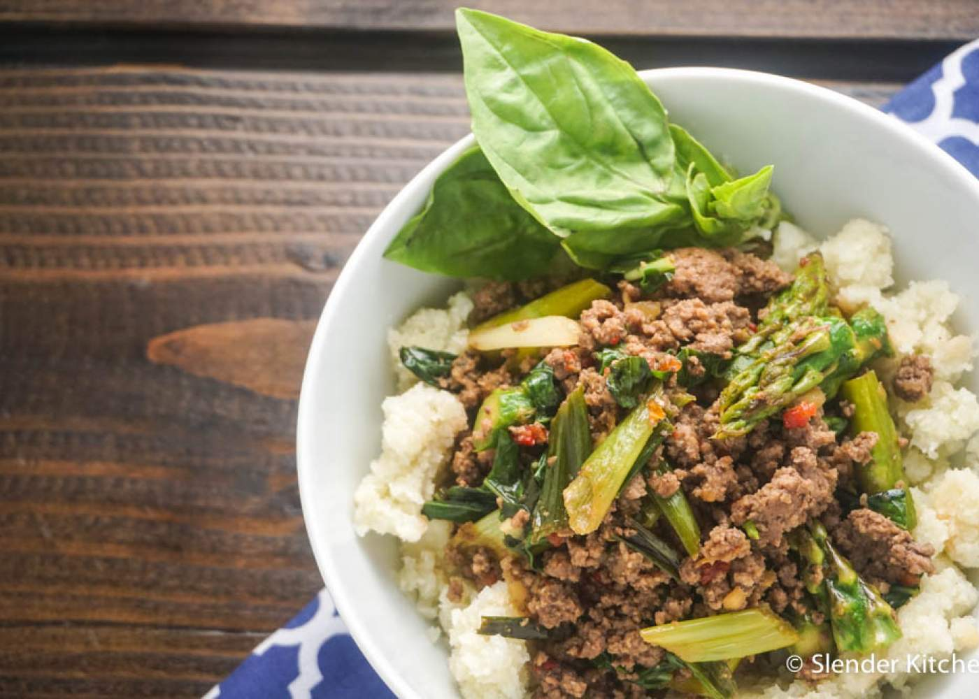 Thai Basil Ground Beef in a bowl with fresh basil and a wooden background.