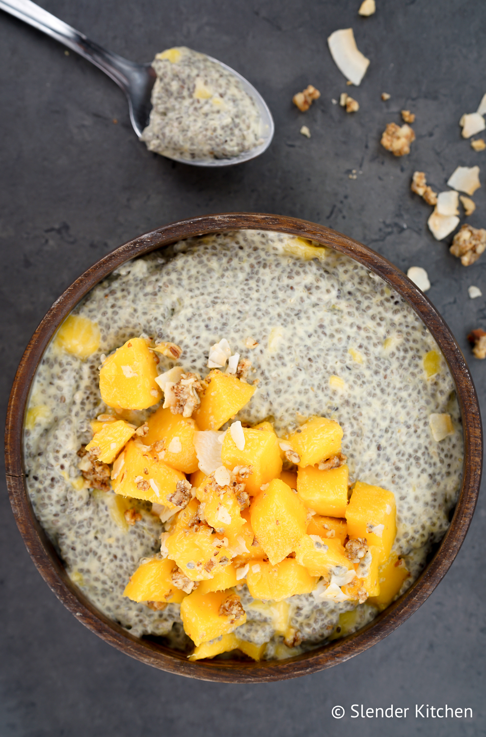 How to make chia pudding with a spoon and granola on a dark slate background.