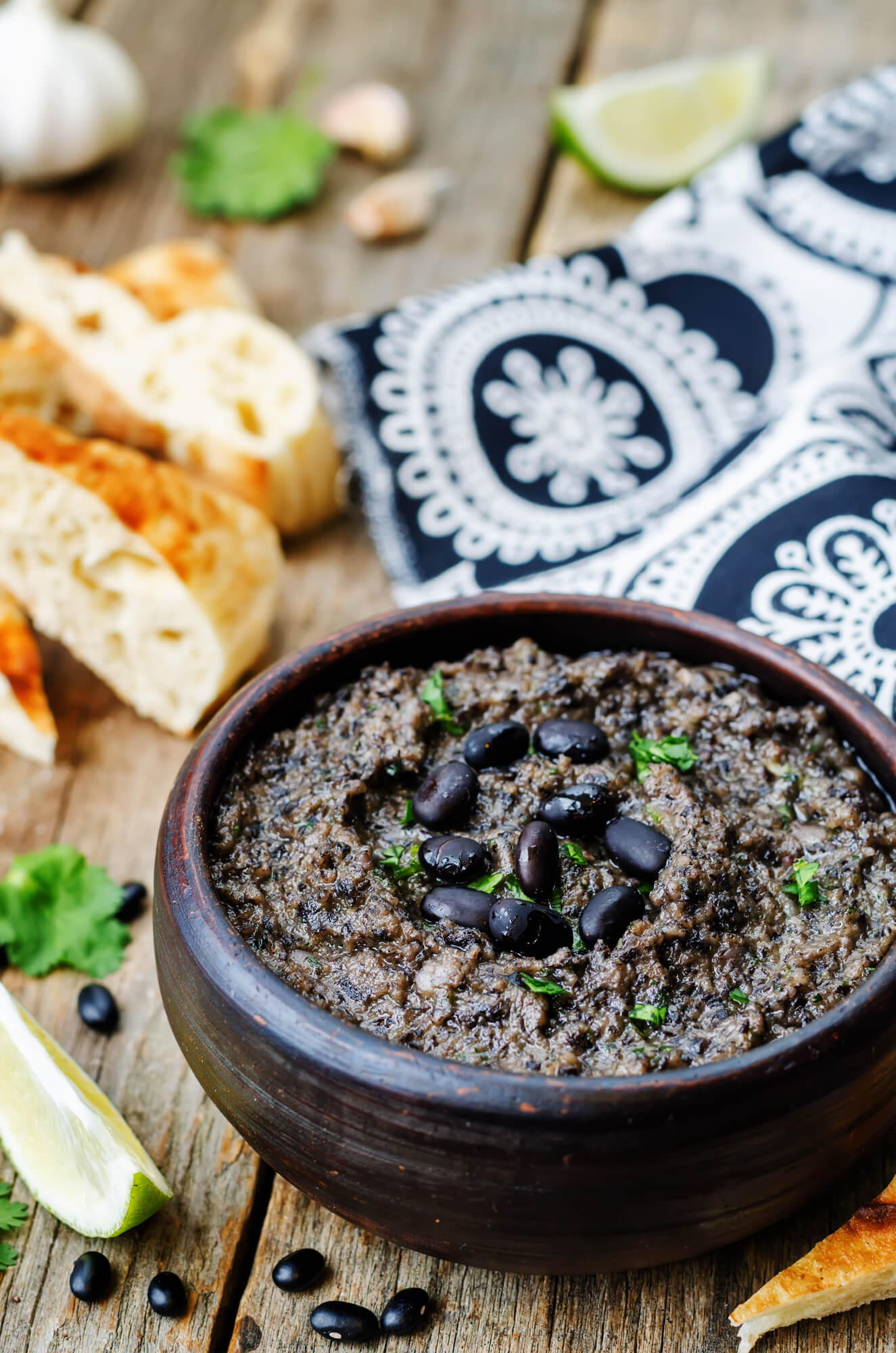 Black Bean Hummus is a wooden bowl with cilantro and garlic.