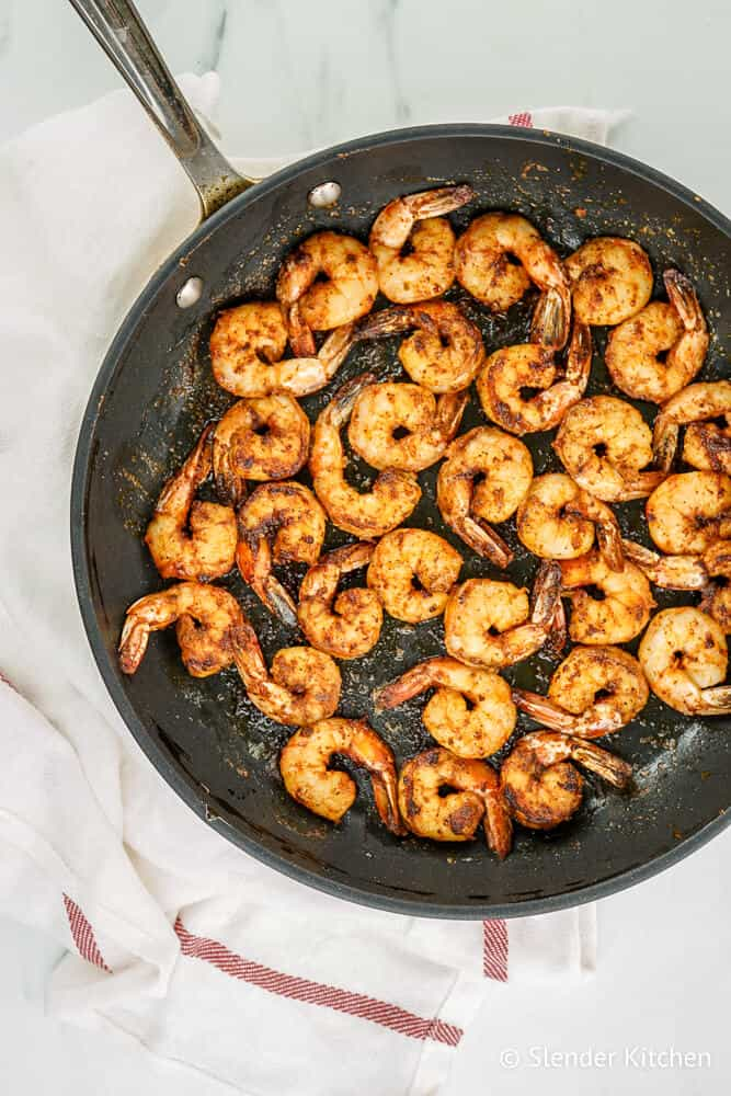 A skillet with blackened shrimp and a red and white napkin.