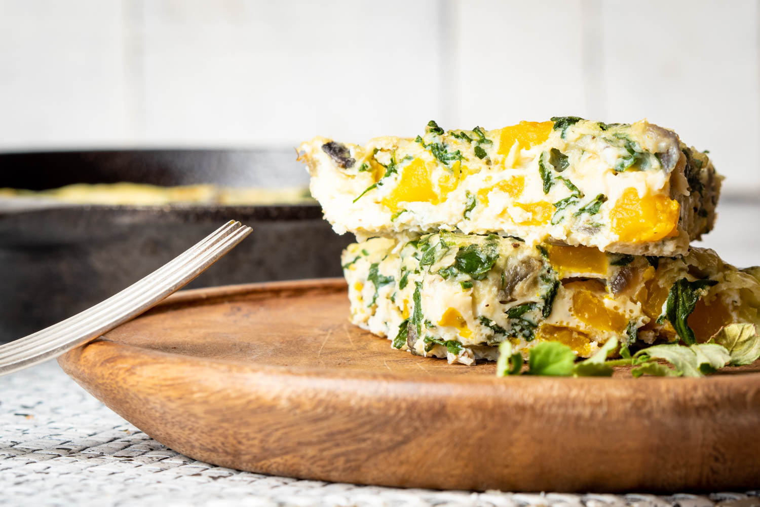 Side view of butternut squash and spinach egg casserole with blurred background.