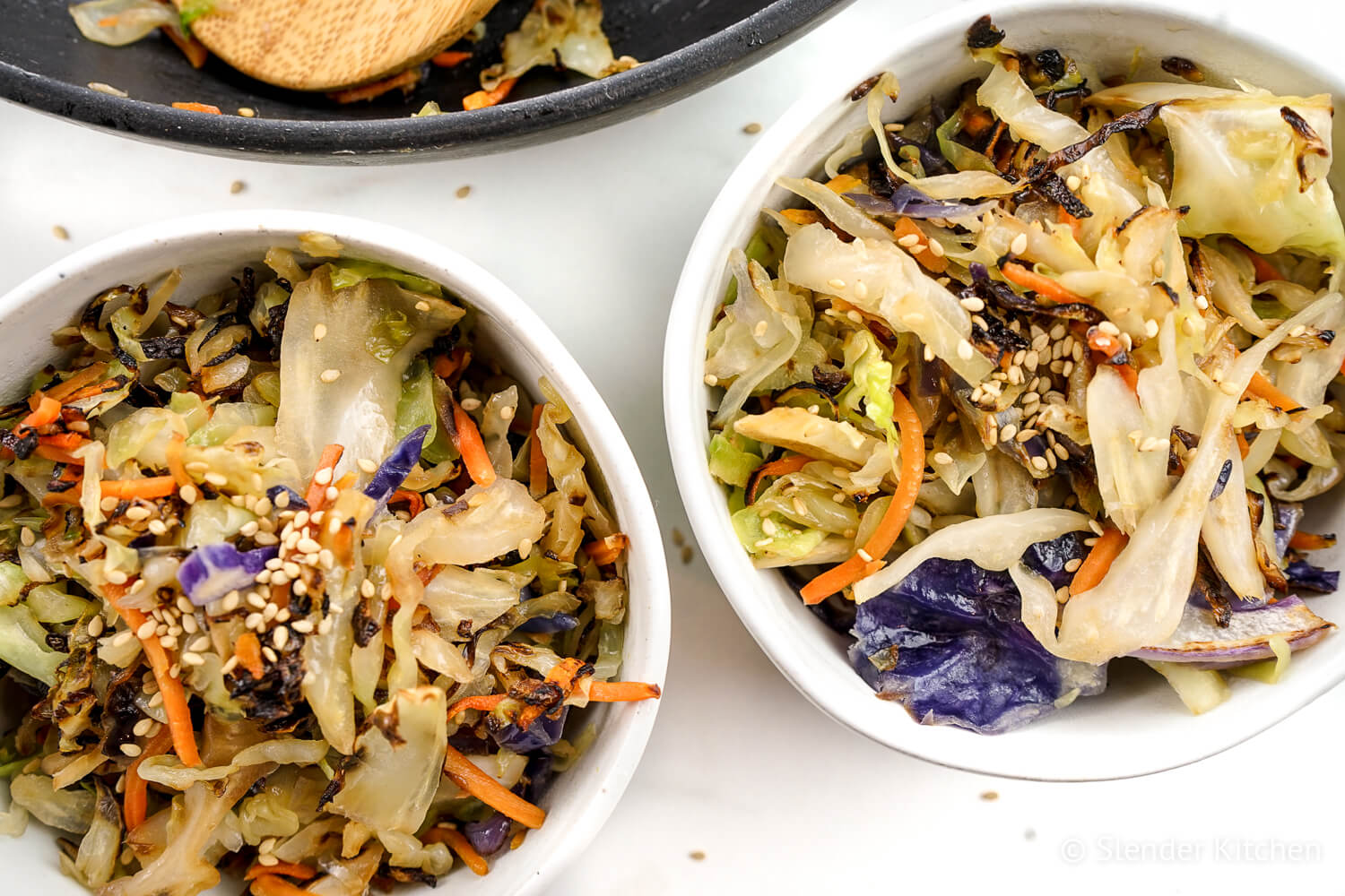 Cabbage stiry fry in two white bowls topped with sesame seeds.