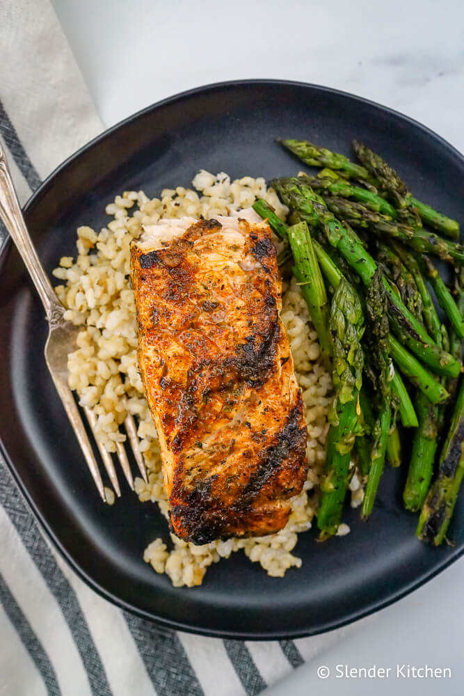 Cajun Salmon with brown rice and grilled asparagus on a black plate.