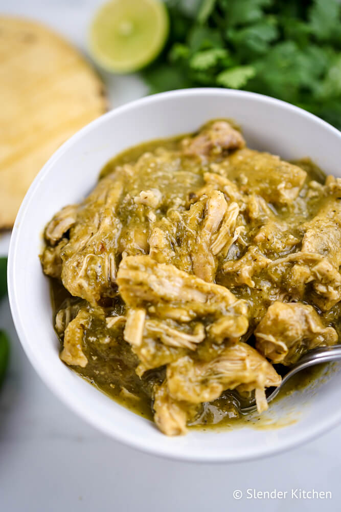 Chile verde recipe in a white bowl with tortillas, cilantro, and limes.