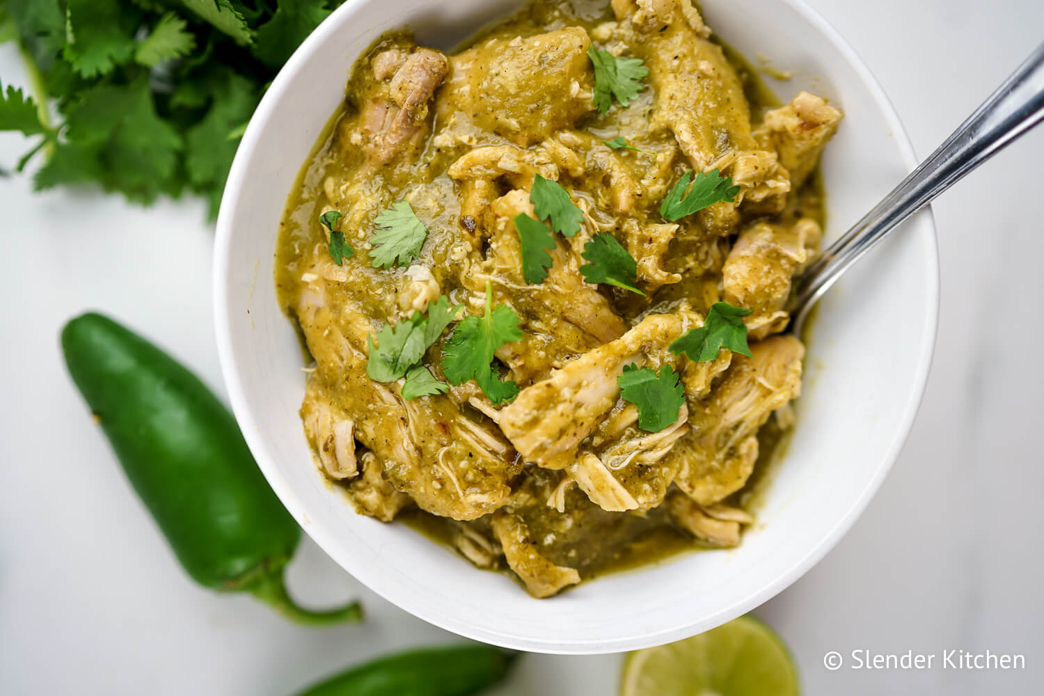 Slow Cooker Chile Verde in a bowl with cilantro and tortillas.