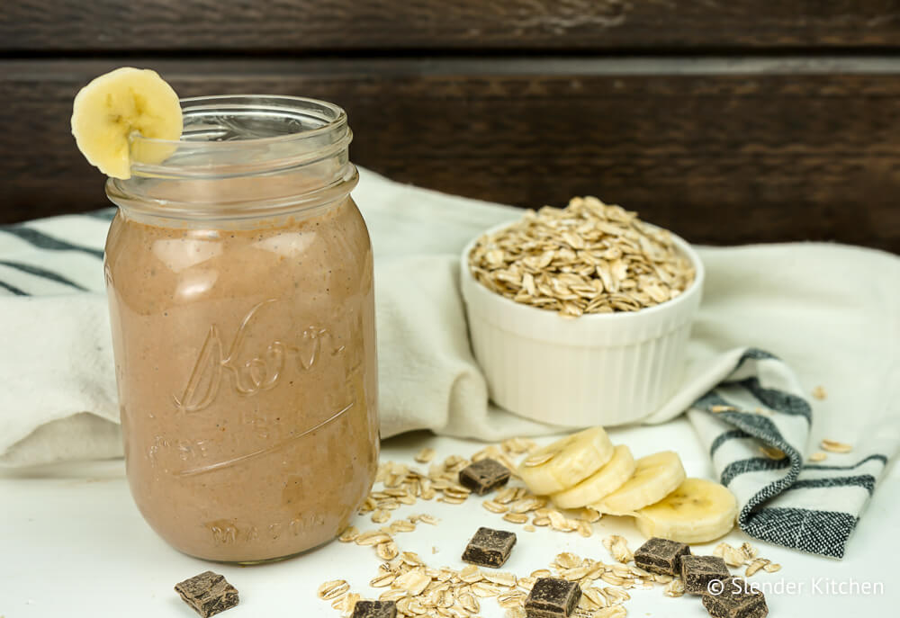 Chocolate smoothie with banana in a glass on a wooden table.