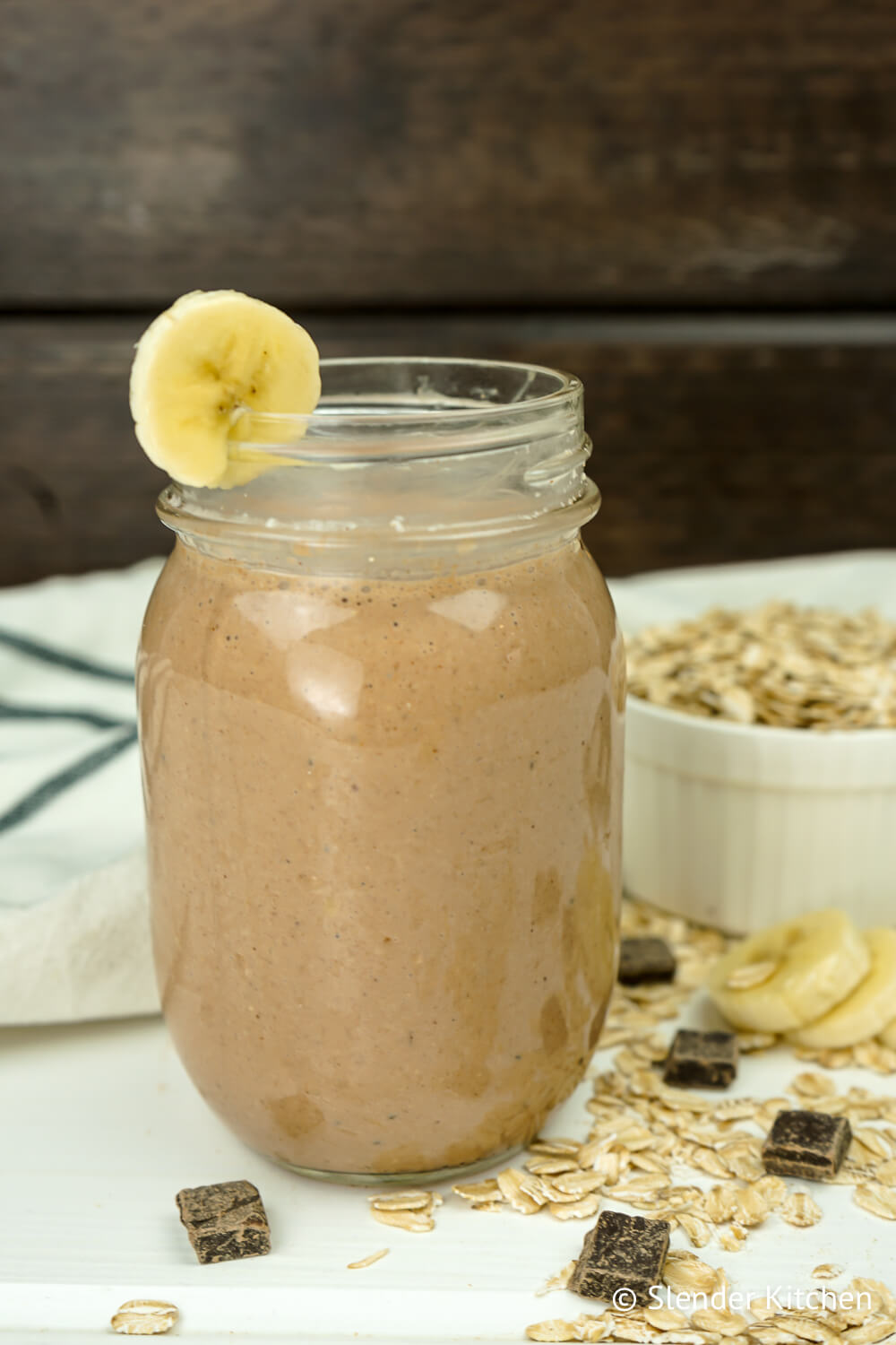 Chocolate banana smoothie in a mason jar with loose oats and chocolate.