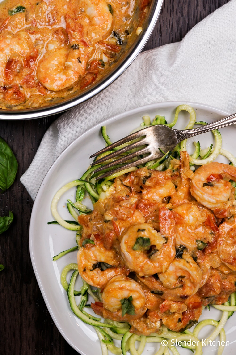 Paleo Creamy Coconut Shrimp and Tomato in a pan with zucchini noodles.
