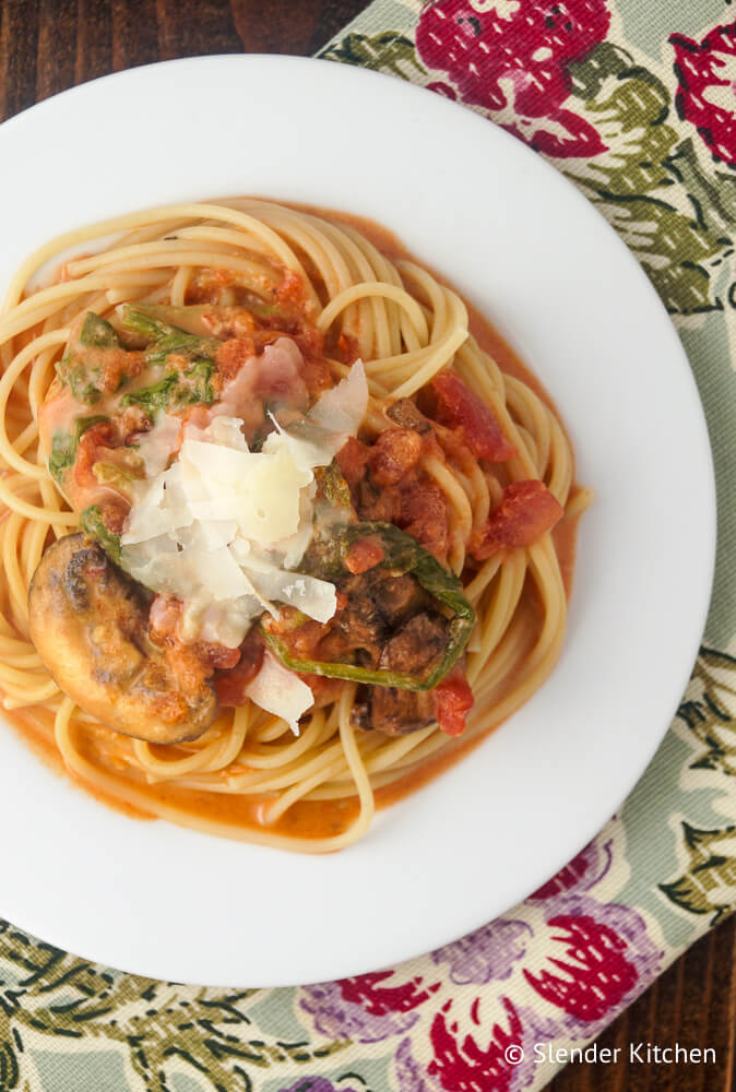 Creamy tomato and spinach pasta with mushrooms on a white plate with a flowered napkin.
