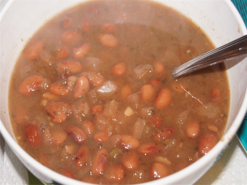 Pinto beans in broth in a white bowl.