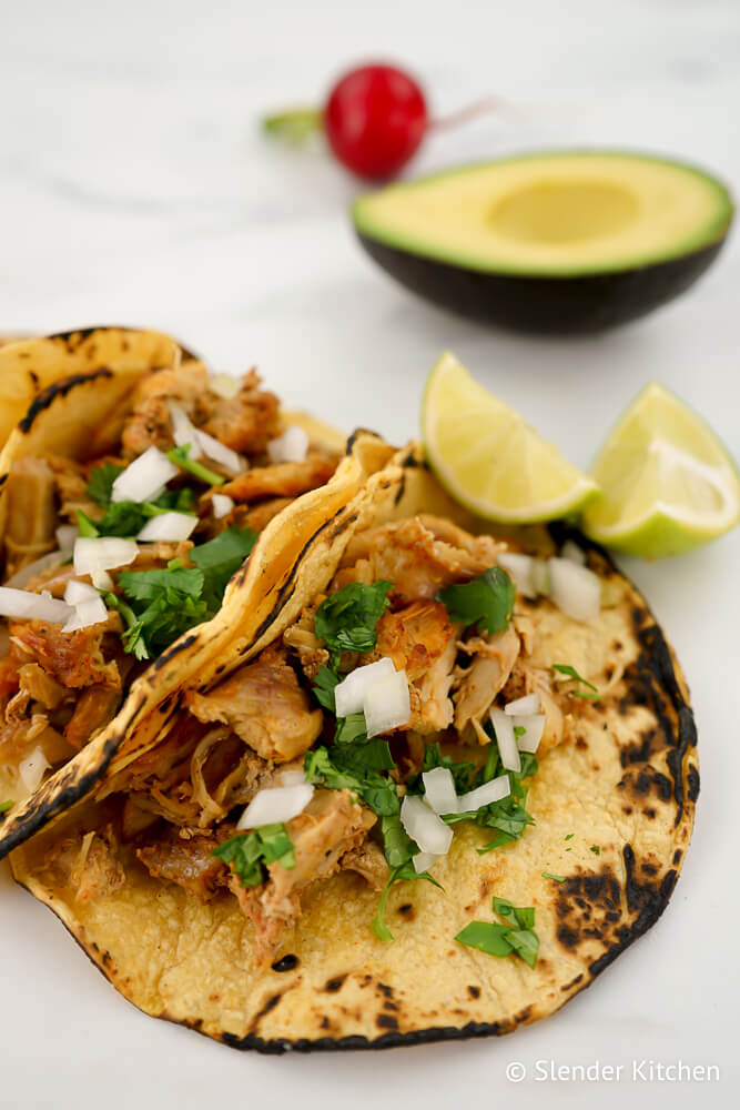 Slow Cooker Carnitas in corn tortillas with cilantro and onion.
