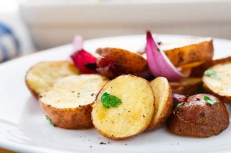 Grilled potatoes with onions on a white plate.