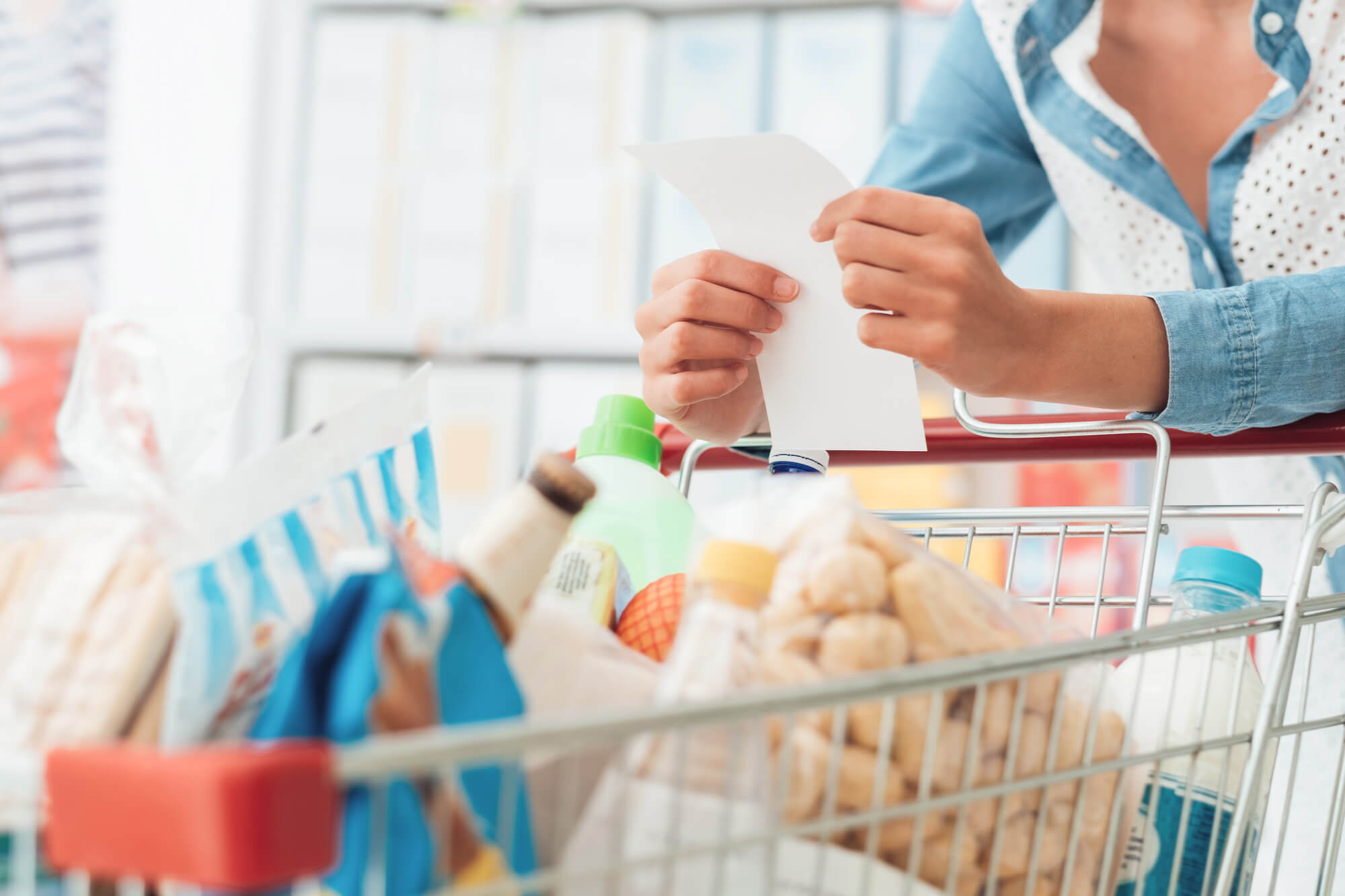 Grocery cart with woman with a list in her hand.
