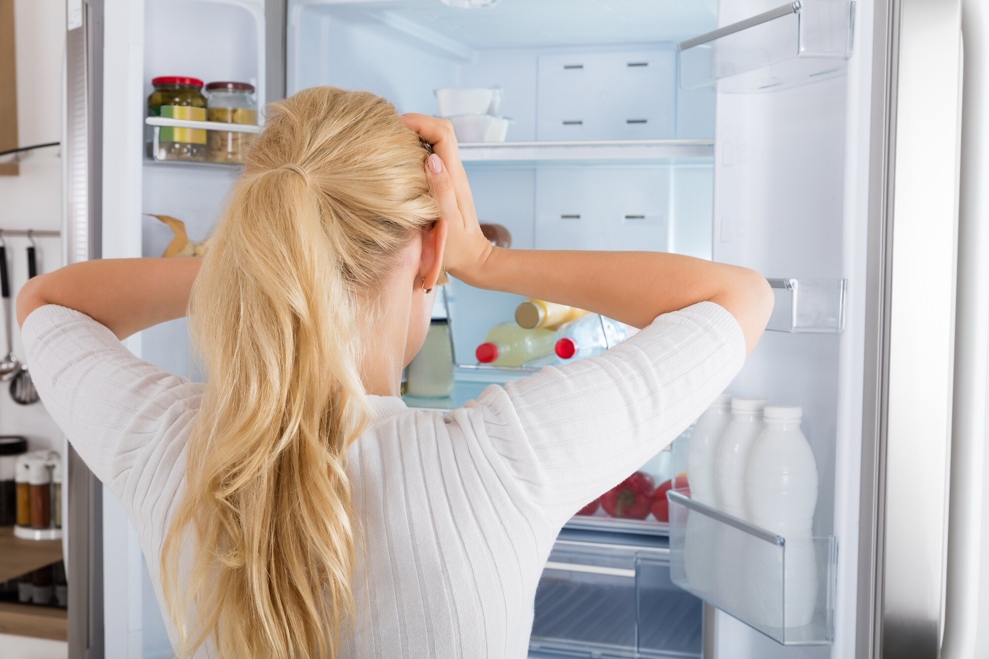 Woman looking into fridge with hands on head trying to figure out what to eat.