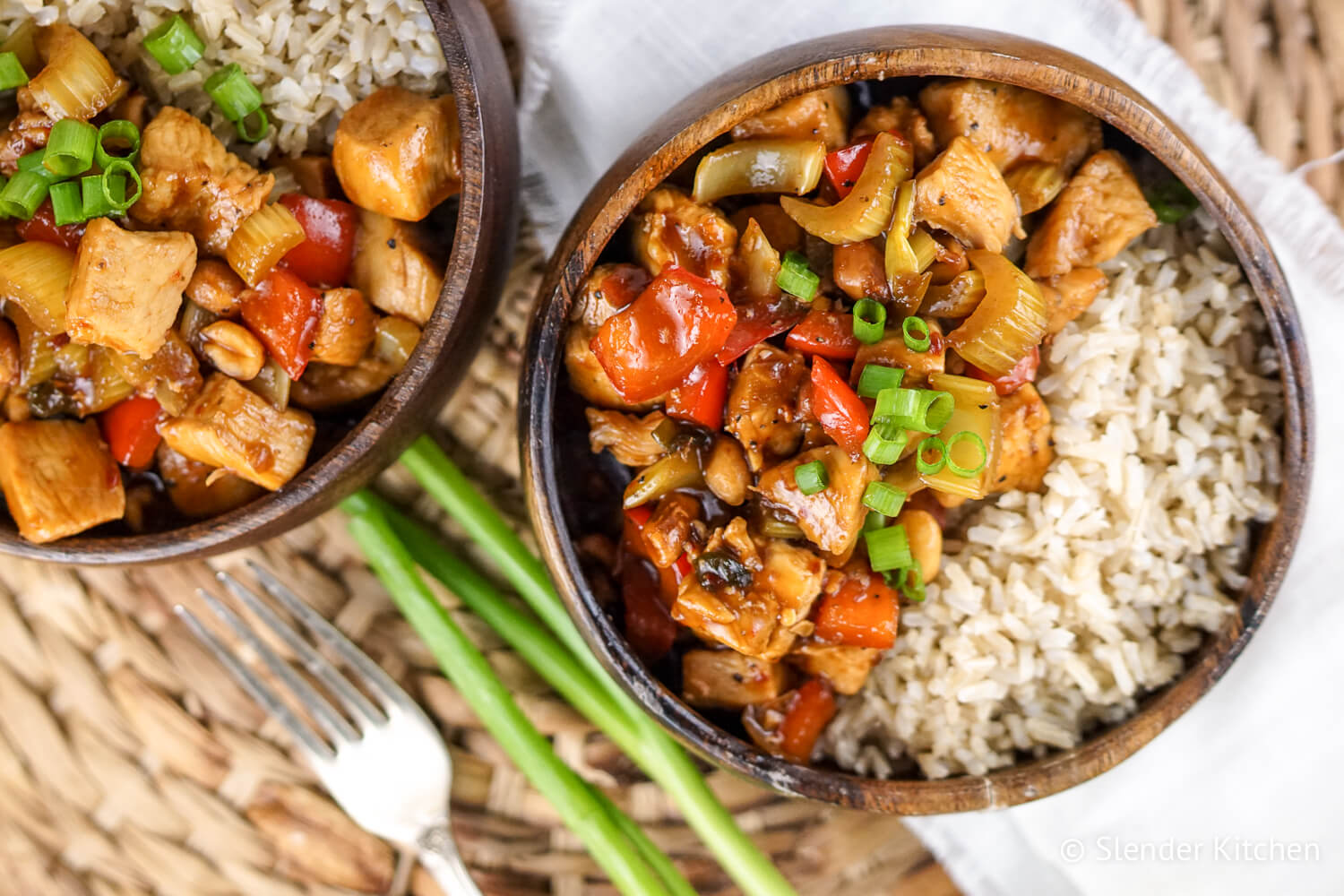 Healthy Kung Pao Chicken with brown rice in a wooden bowl.