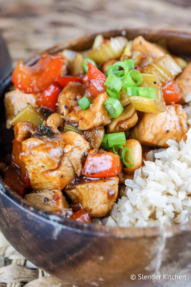 Easy Kung Pao Chicken in a bowl with peanuts and green onions.