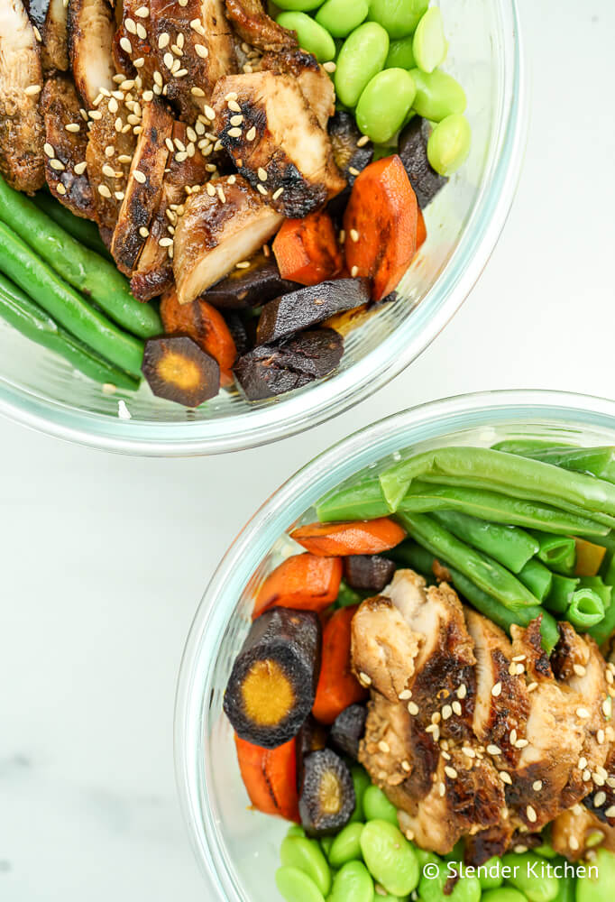 Honey soy glazed chicken in a glass bowl with carrots, edamame, and green beans.