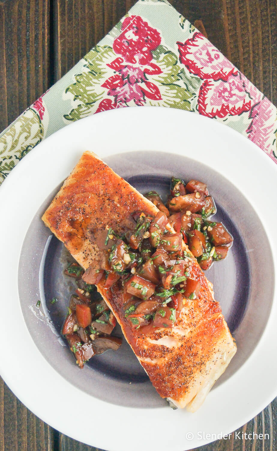 Italian salmon with tomato basil salsa on a white plate with a flowered napkin.