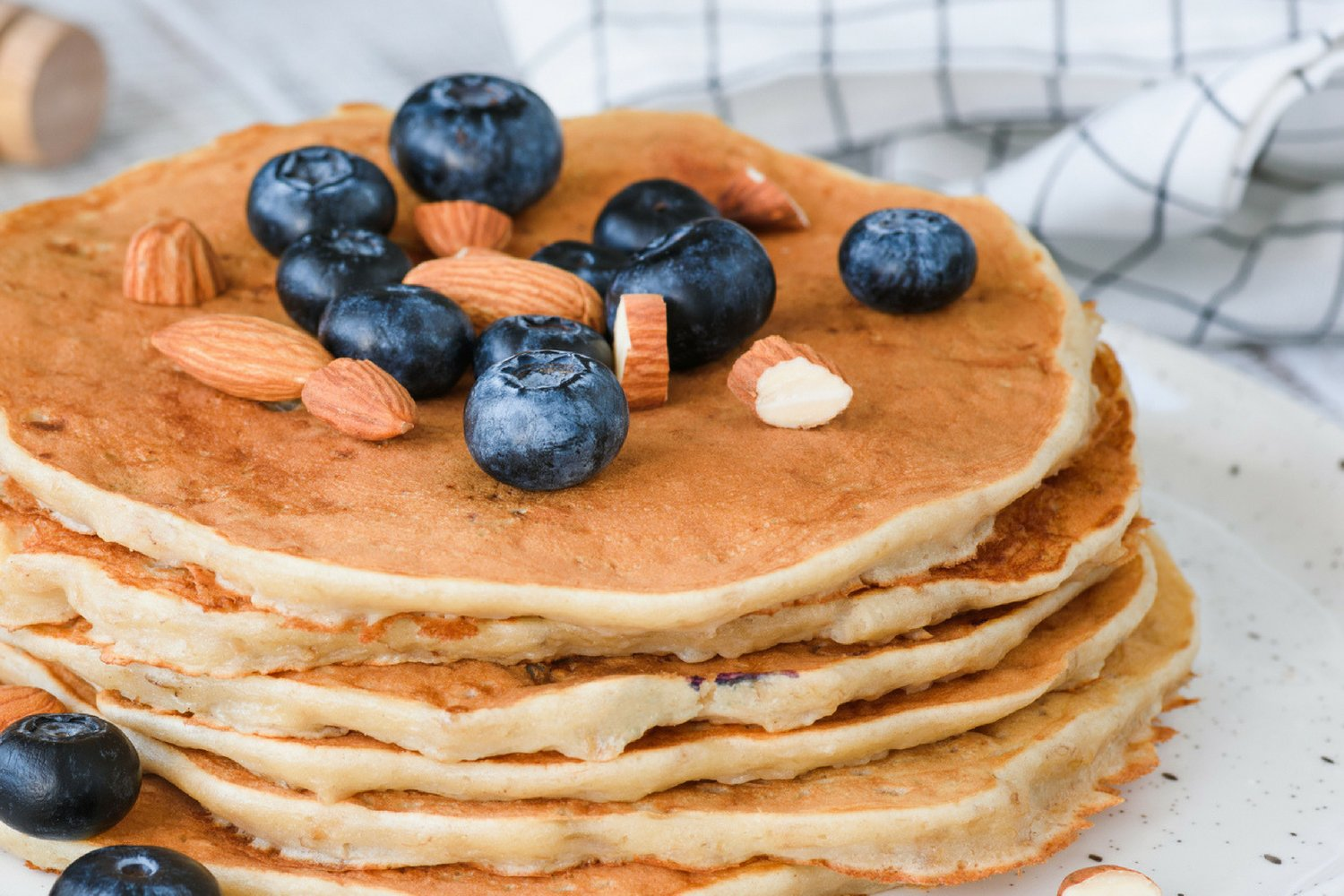 Low carb almond flour pancakes with blueberries and almonds on a white plate.