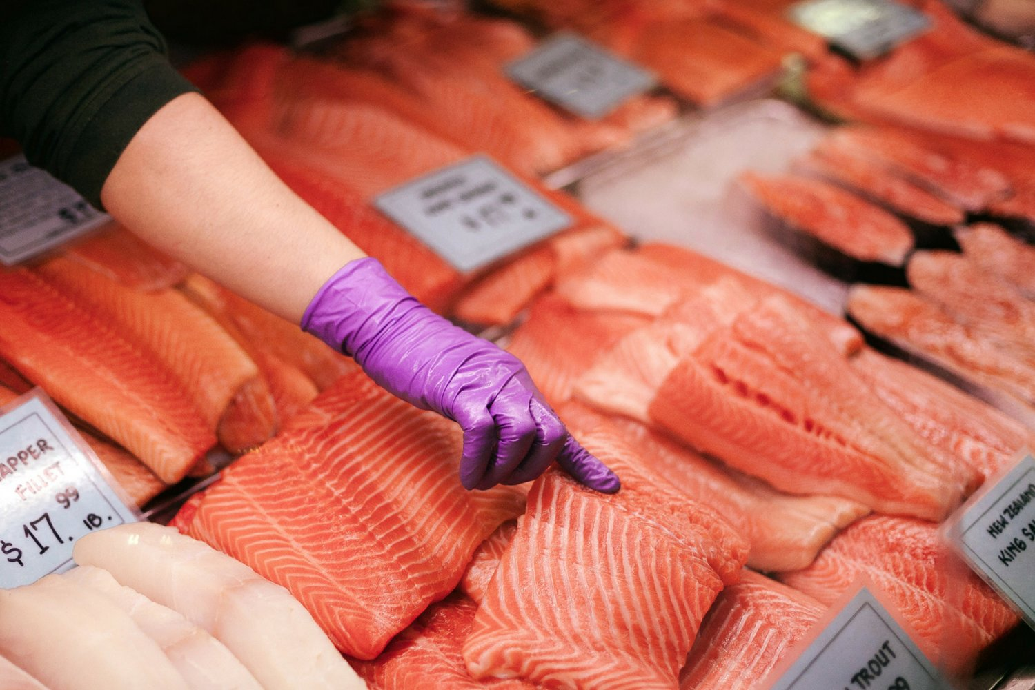 Different types of salmon on ice at a fish market and a hand picking up a filet.