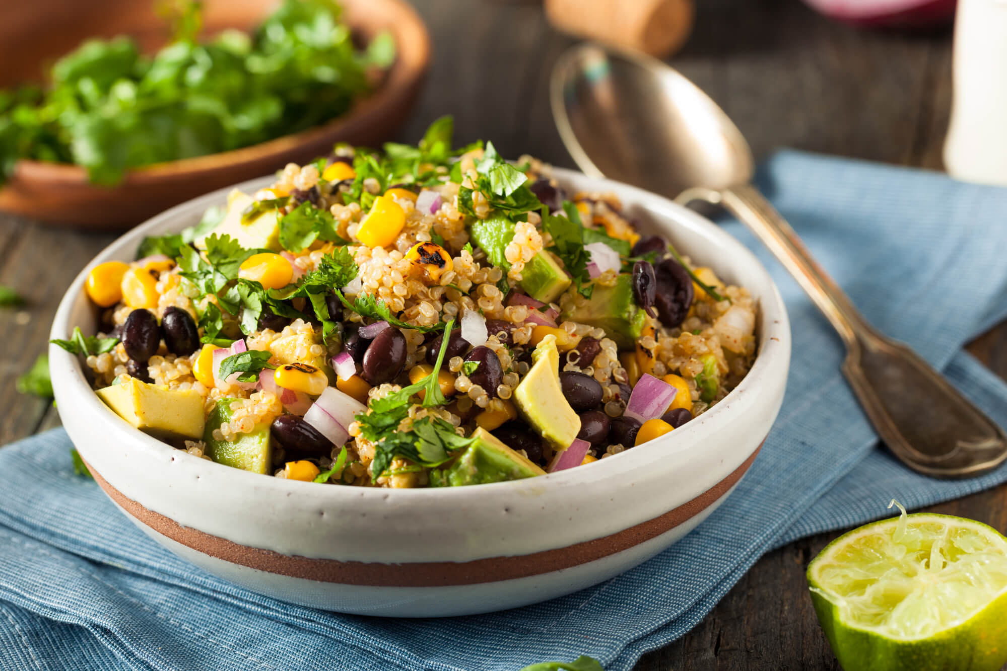 Southwest Quinoa and Bean Salad in a wooden bowl with cilantro in the background.