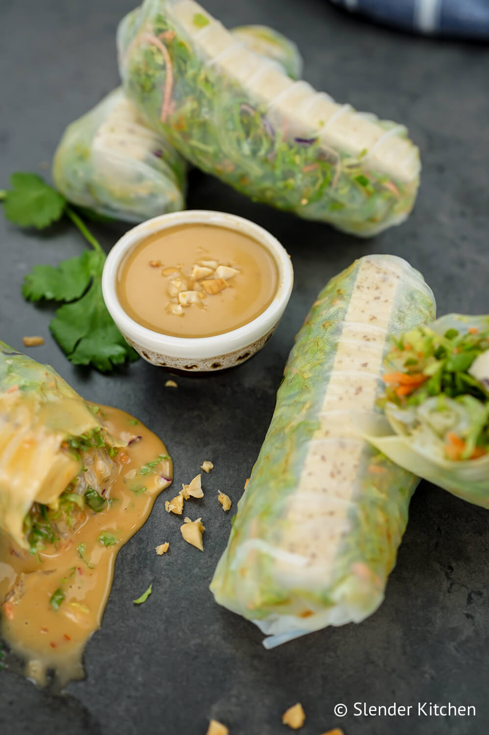 Spring rolls on a gray slate background with peanut sauce and cilantro.
