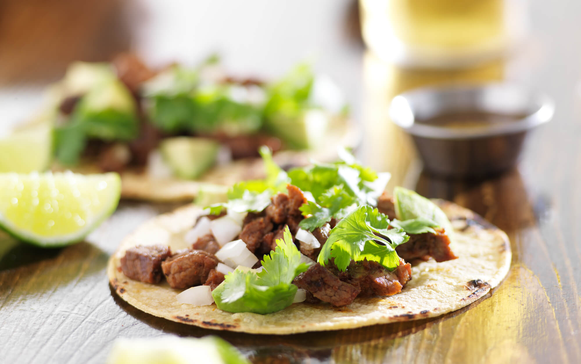 Close up of a steak taco on a corn tortilla with onion and cilantro.