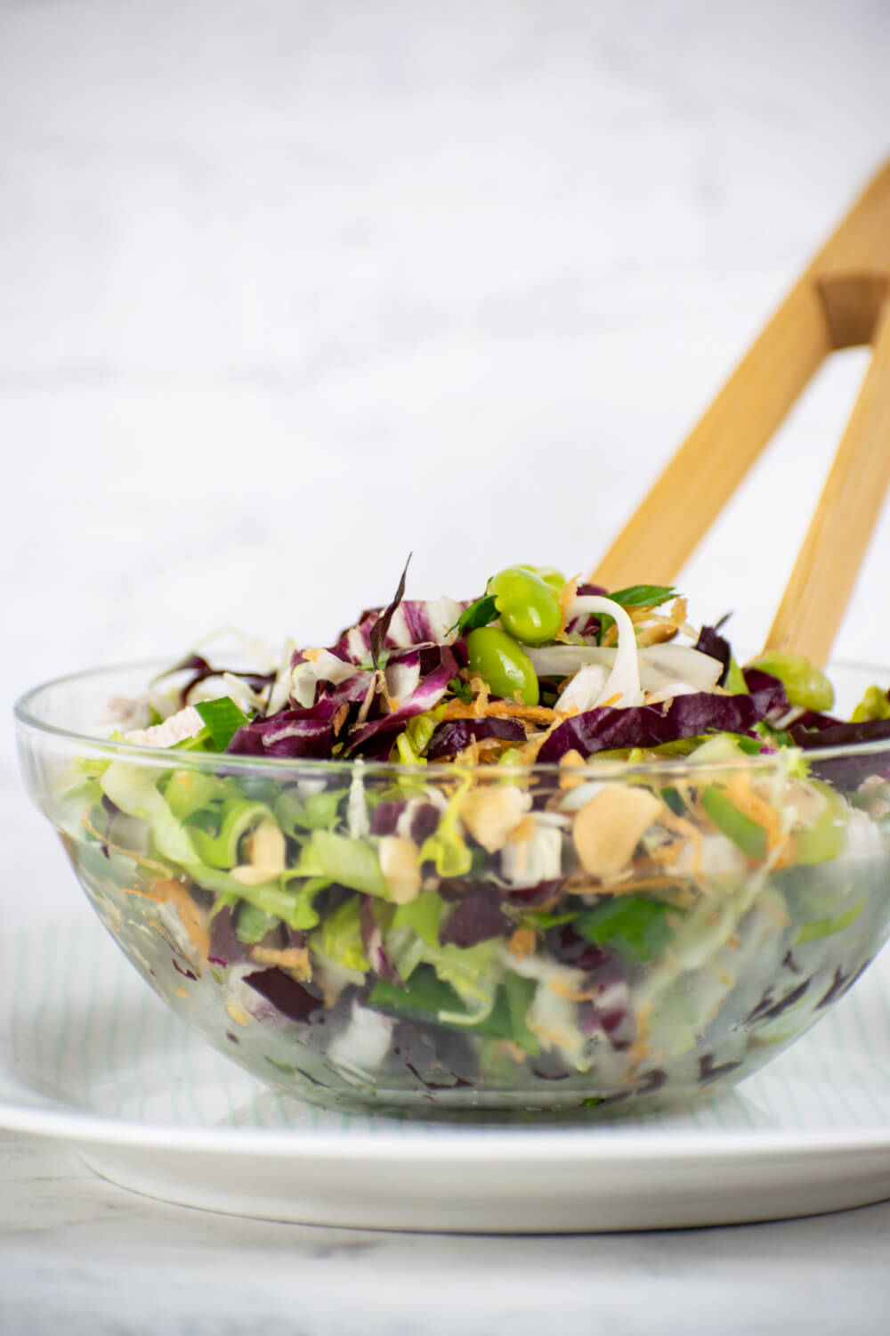 Thai Chili Chicken Salad with cabbage, edamame, carrots, and lettuce in a glass bowl with chopsticks.