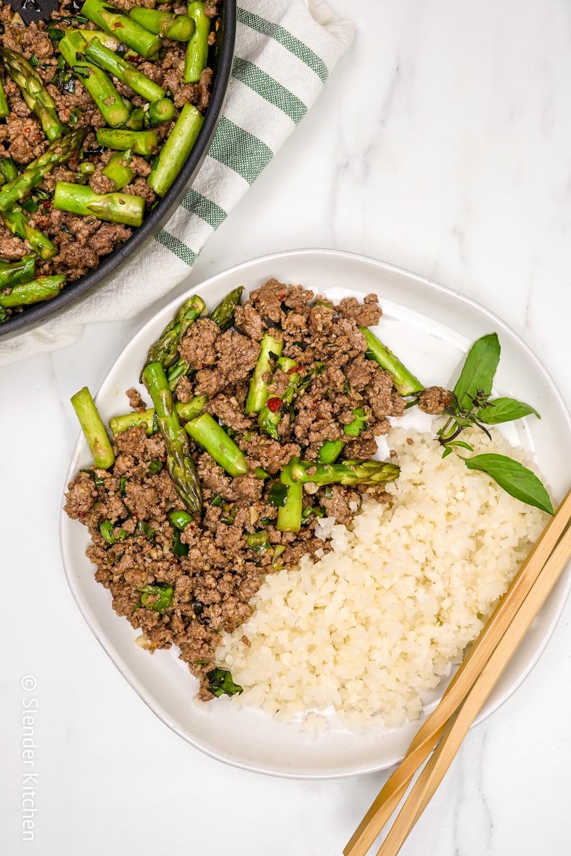 Thai Beef Basil Stir Fry on a plate with cauliflower rice and chopsticks.