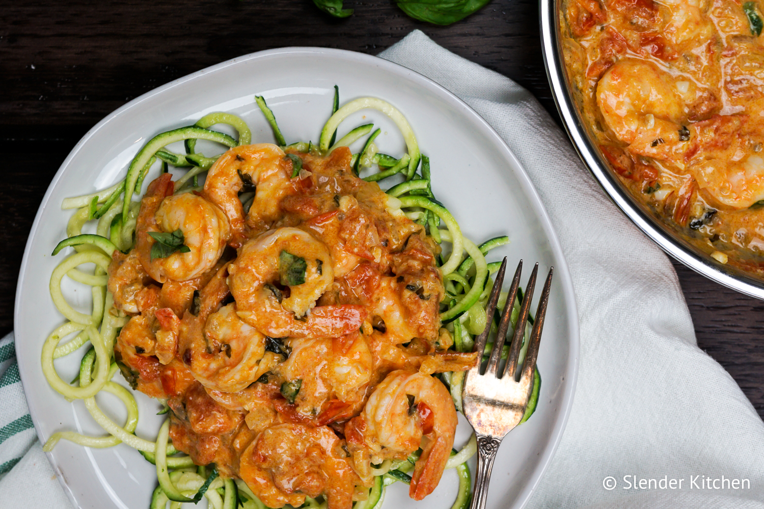 Creamy Coconut and Tomato Shrimp on a plate with zucchini noodles.