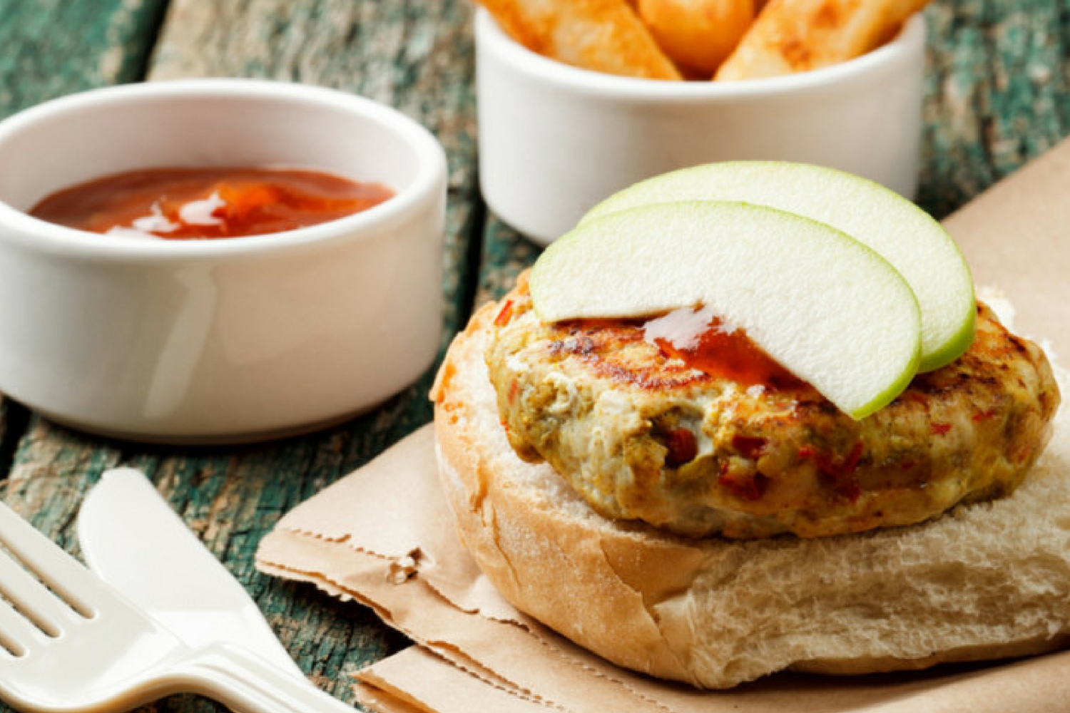 Turkey Apple Burgers on a plate with sliced green apples.