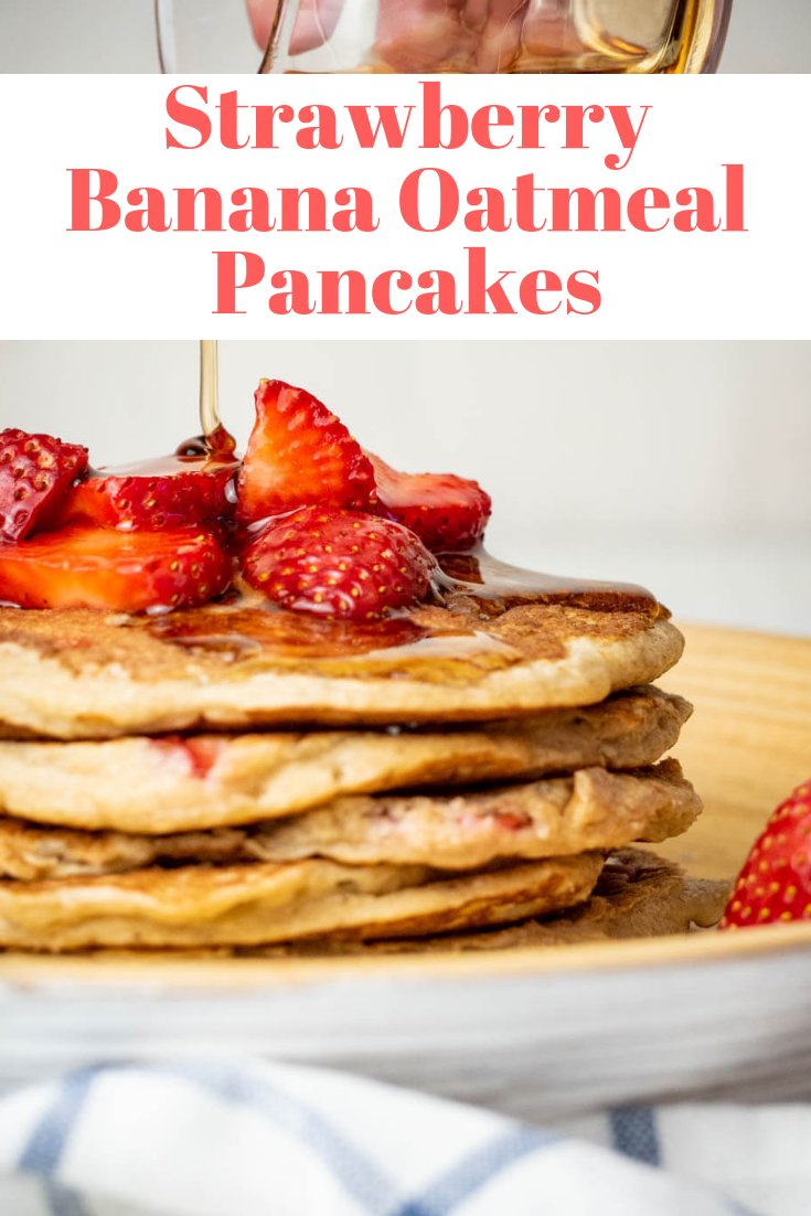 Banana oatmeal pancakes with strawberries and maple syrup.