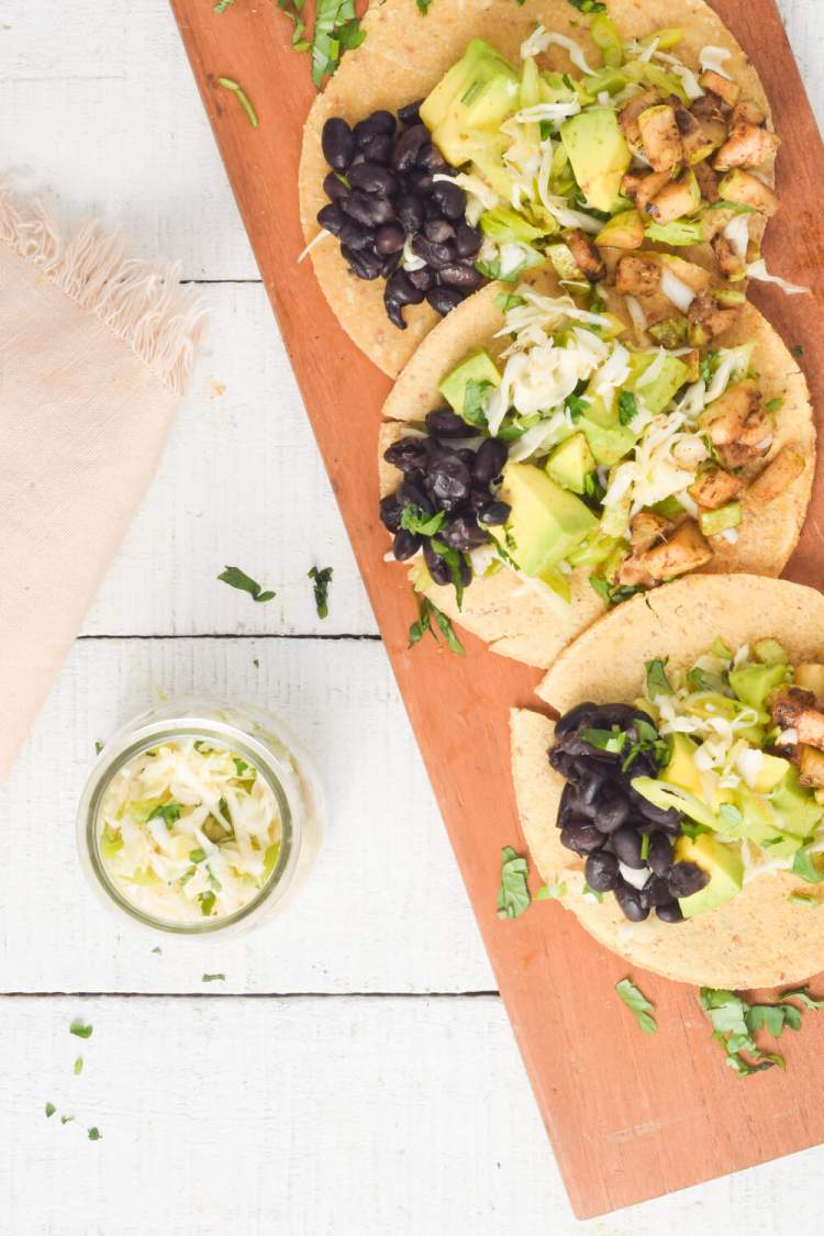 Three vegetarian black bean and zucchini tacos with cabbage slaw and avocado.