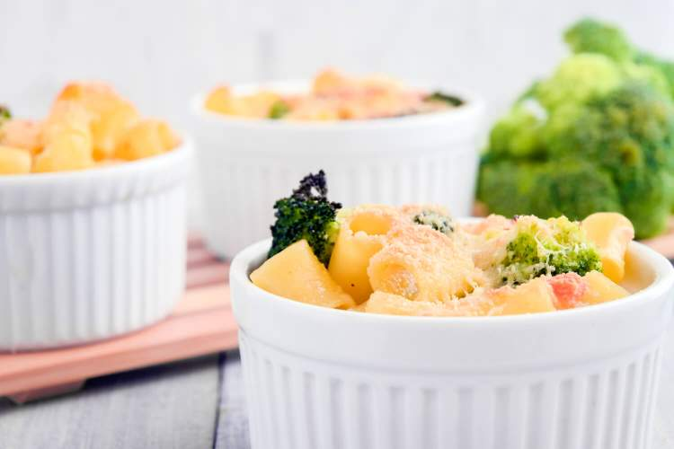 Broccoli mac and cheese in ramekins with pasta, broccoli, and cheese sauce.