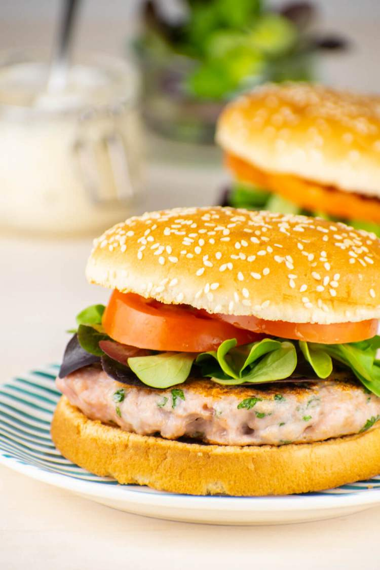Caesar Chicken Burgers on a sesame seed bun with dressing, tomatoes, and lettuce.