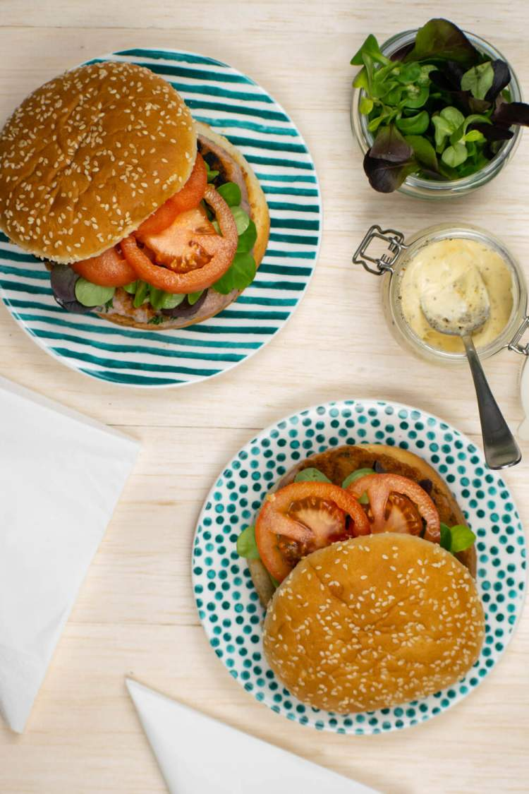 Chicken burgers with caesar dressing on buns with tomato and lettuce.