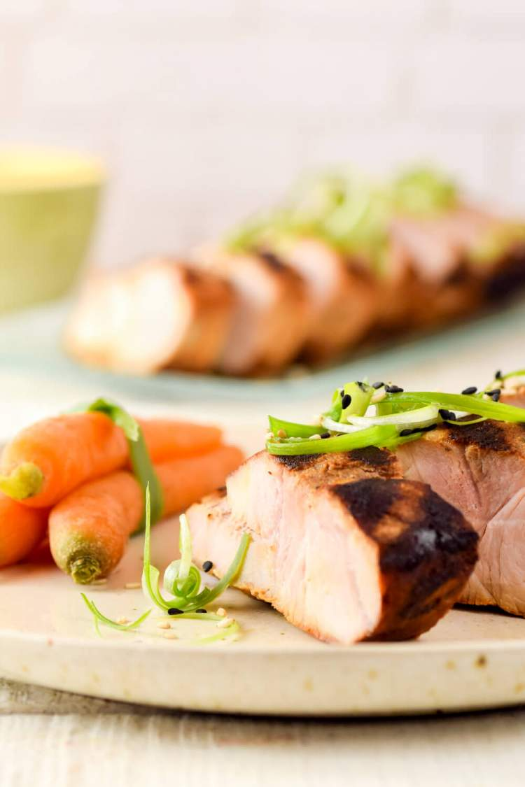 Grilled Asian pork tenderloin with green onions and carrots on a plate.