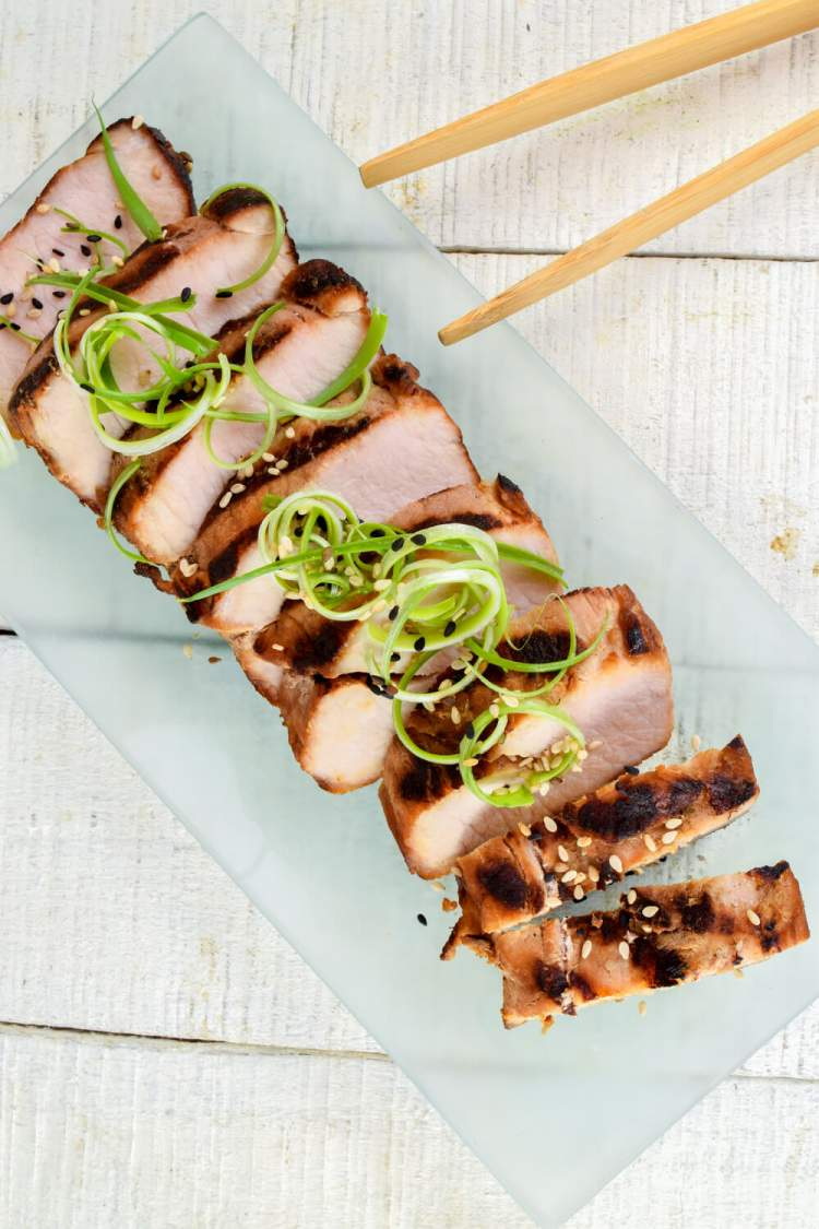 Grilled pork i an Asian marinade on a plate with sesame seeds and scallions.