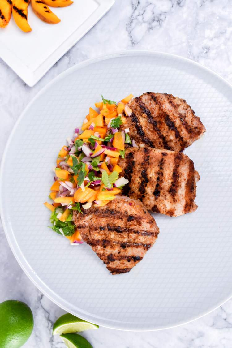 Grilled pork with grilled peaches and salsa on a white plate/