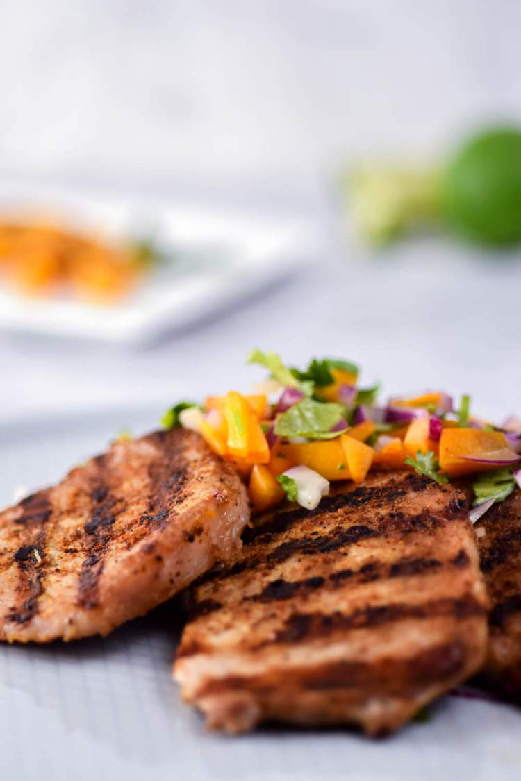 Grilled pork chops with a homemade spice rub topped with peach salsa.