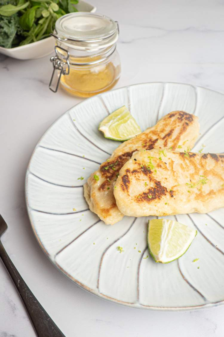 Honey Lime Tilapia with a crispy coating and flavored with honey and lime zest on a plate with a fork.