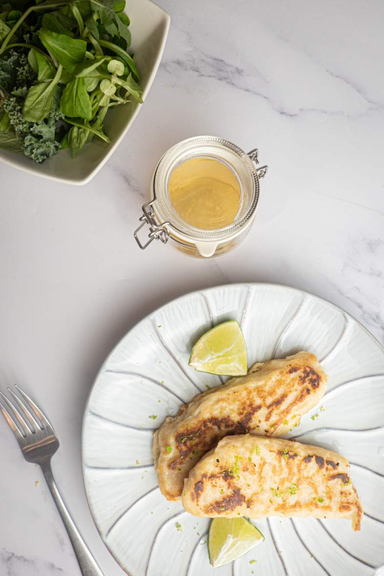 Tilapia with honey and lime on a plate with a bowl of greens and a fork.