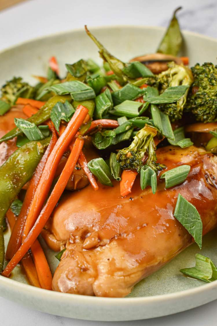 Teriyaki chicken and vegetables with chicken thighs, broccoli, carrots, sugar snap peas, and green onions.