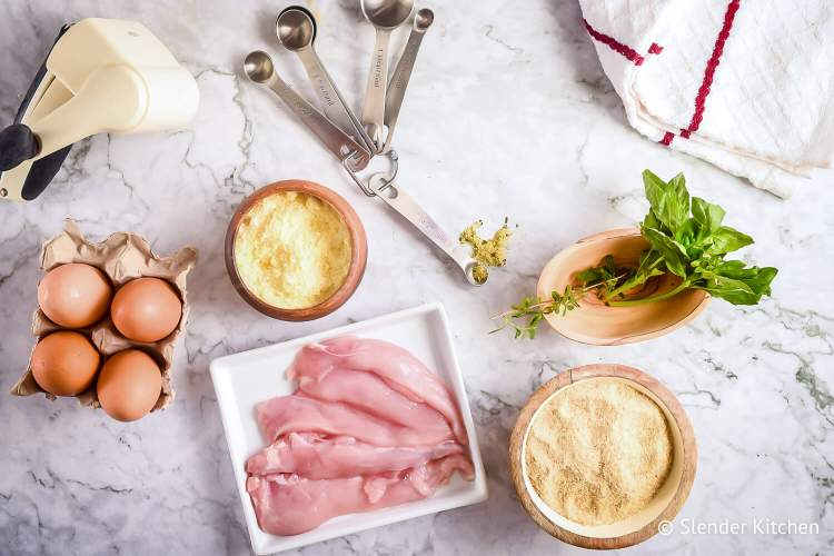 Ingredients to make Parmesan Crusted Chicken including cheese, egg whites, chicken breast, basil, and oregano.