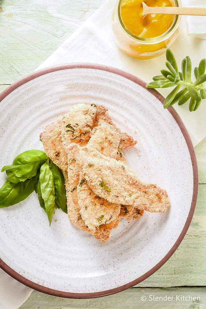 Parmesan chicken on a white plate with basil and a small jar of mustard.