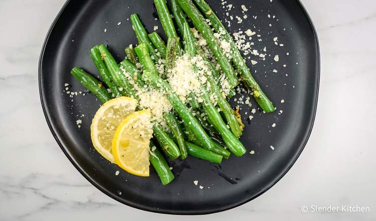 Roasted green beans with Parmesan cheese, lemon, and garlic on a plate.